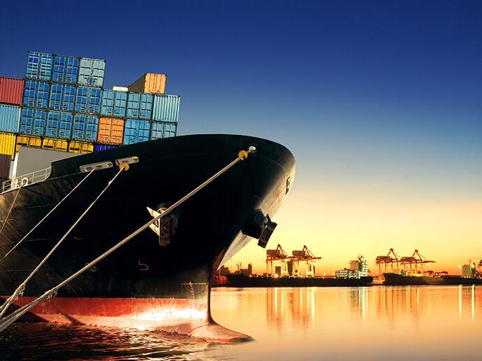 Bow of docked cargo ship at dusk