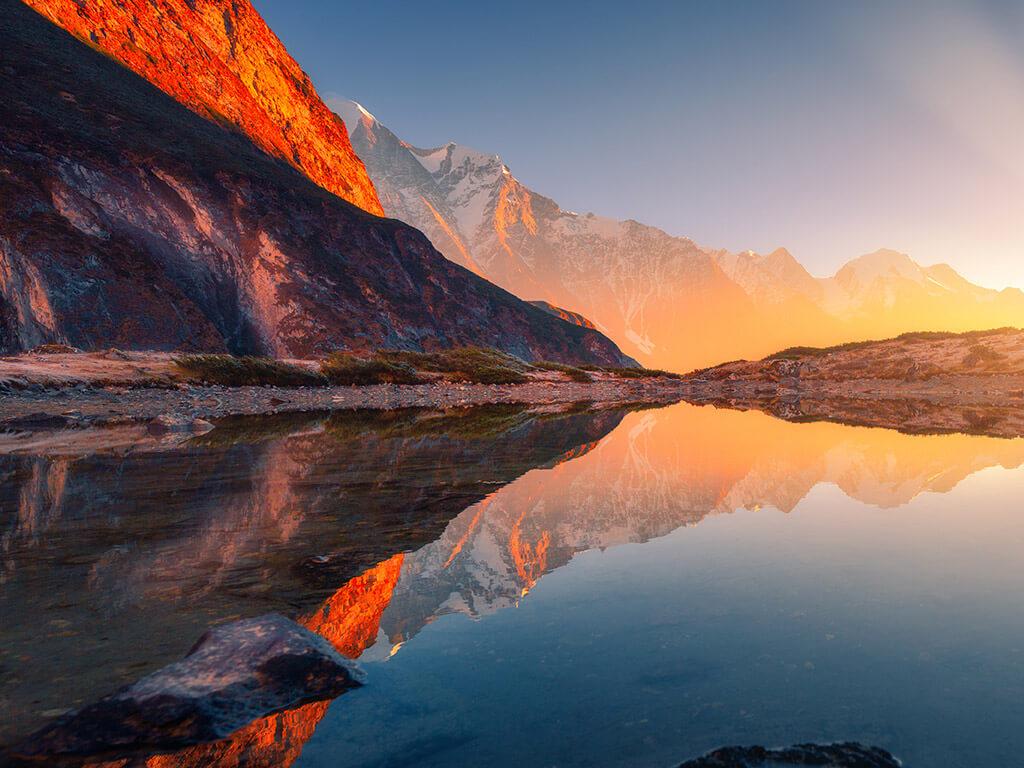 Scenic lake reflecting mountains illuminated by a sunset